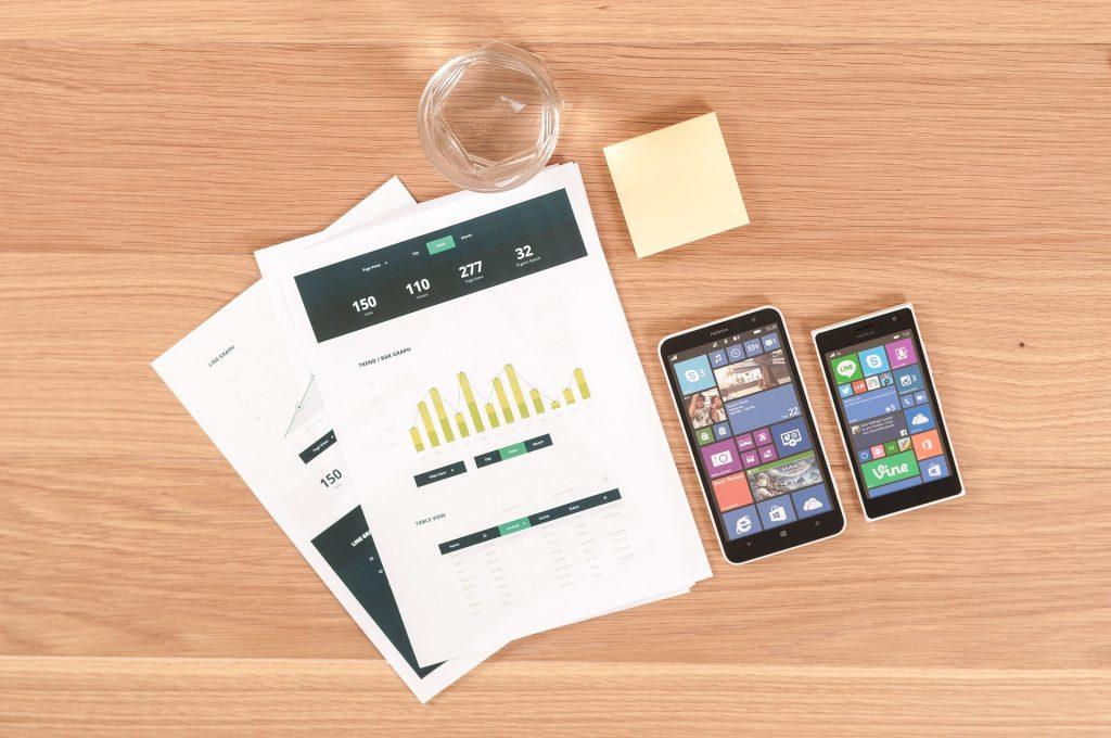 Téléphones posés sur une table à côté de documents